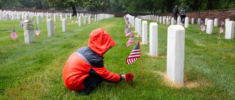 Placing flowers in the rain at Alexandria National Cemetery