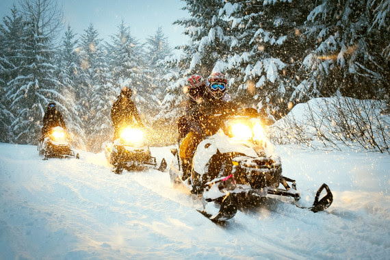 Snowmobiles moving on a snow path at dusk.