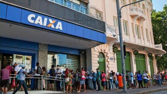 Pessoas fazem fila para coletar auxílio emergencial em meio à pandemia de coronavírus