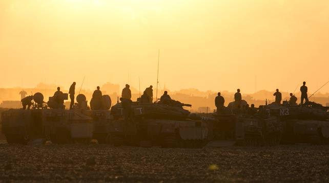Los soldados israelíes permanecen sobre los tanques y transportes blindados en el norte de la Franja de Gaza.