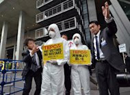 Members of environmental group Greenpeace wearing radiation protection suits are asked by Tokyo Electric Power Co (TEPCO) staff to move away from the entrance to TEPCO shareholders meeting in Tokyo, on June 26, 2014