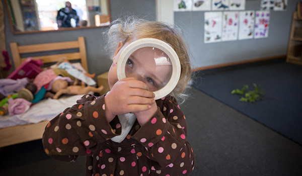 Little girl playing with a magnifying glass