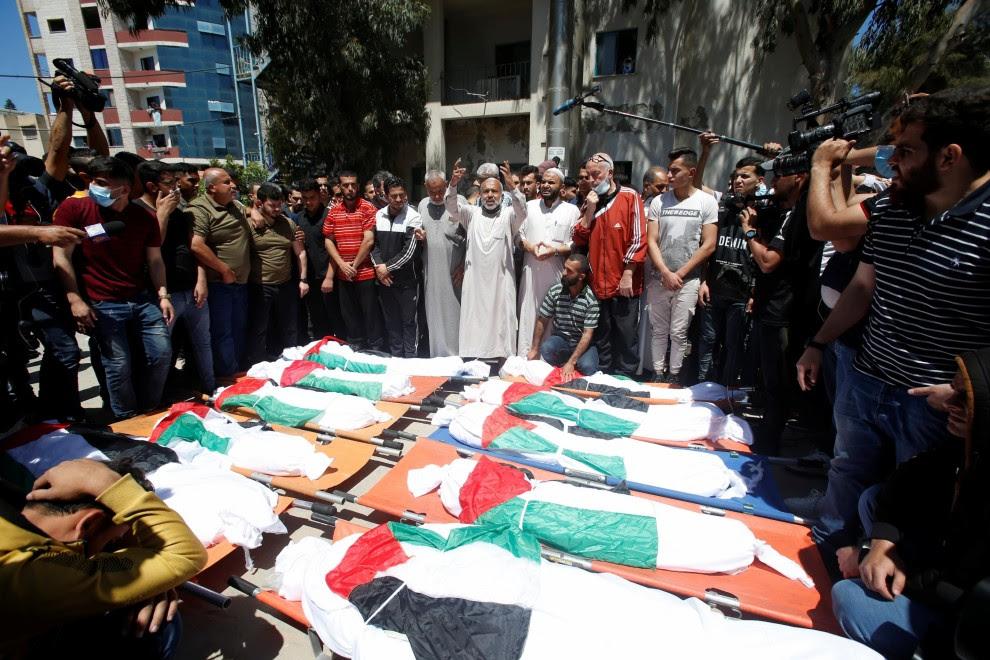15/05/2021. Varias personas se acercan a los cadáveres de los palestinos asesinados este sábado por las fuerzas israelíes. - Reuters
