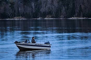 A fisherman enjoys an evening fishing from his boat.