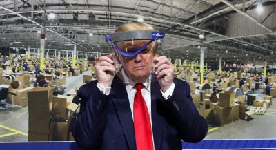 US President Donald Trump holds up a protective face shield during a tour of the Ford Rawsonville Components Plant that is manufacturing ventilators, masks and other medical supplies during the coronavirus disease (COVID-19) pandemic in Ypsilanti, Michigan, 21 May 2020 (Photo: REUTERS/Leah Millis).