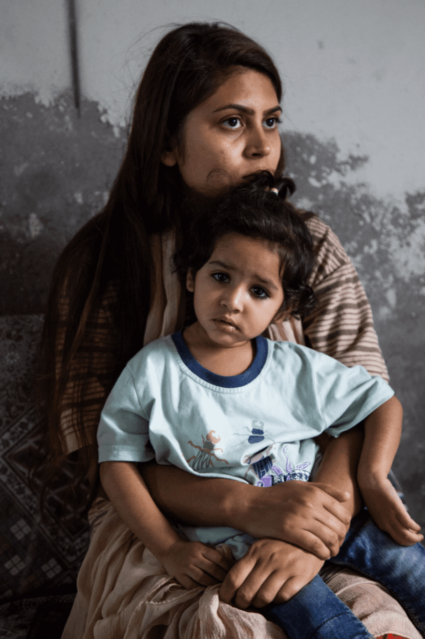 a woman sits with a young family member on her lap