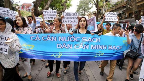 """Người dân Việt Nam xuống đường tuần hành với biểu ngữ """"Cá cần nước sạch, dân cần minh bạch"""" tại Hà Nội. Ảnh: EPA"""