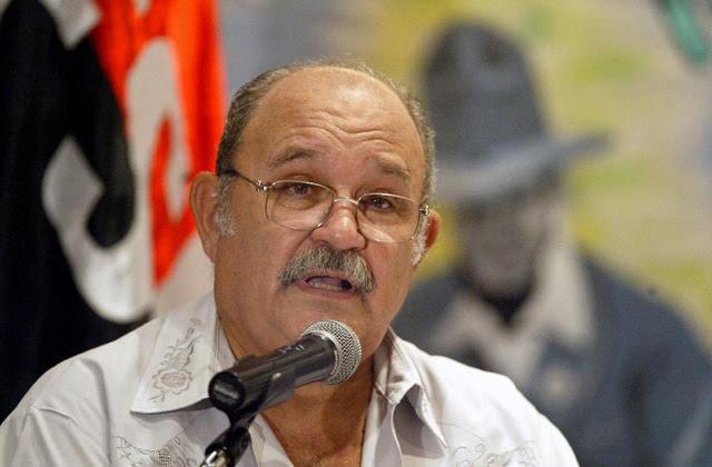 Miguel D'Escoto, ofreciendo una charla delante de la bandera del Frente Sandinista de Liberación Nacional y la imagen del líder nicaragüense Augusto Sandino.