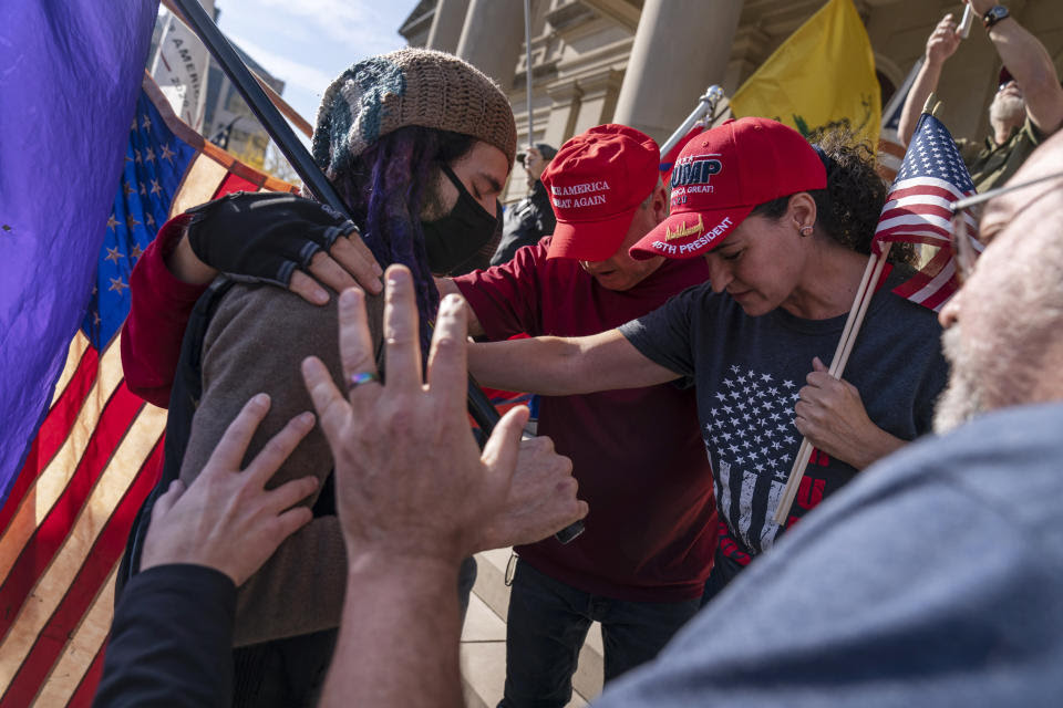 Trump supporters demonstrating during the election results, at right, pray with a counter protester after the presidential election was called for Joe Biden outside the State Capitol in Lansing, Mich., Saturday, Nov. 7, 2020. (AP Photo/David Goldman)