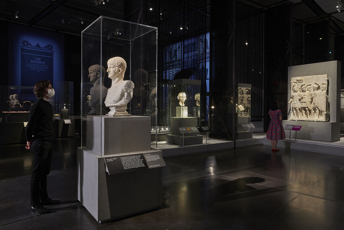 Inside 'Nero: the man behind the myth'. A visitor looks at a marble bust of Nero to the left, and another visitor looks at a sculpture of Roman soldiers in the background. A blue projection can be seen behind.