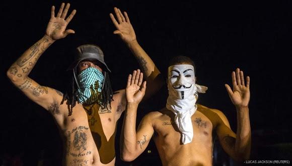 Manifestantes levantan las manos delante de la Policía. Este gesto se ha convertido en el símbolo de las protestas aludiendo a Brown, que recibió seis disparos estando desarmado.