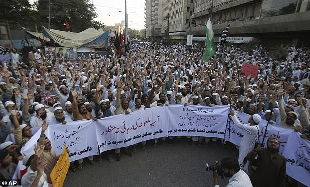 Islamist protesters mount a second day of rallies in Karachi and occupy a street holding a banner which reads: 'Release of blasphemous Asia is unacceptable'