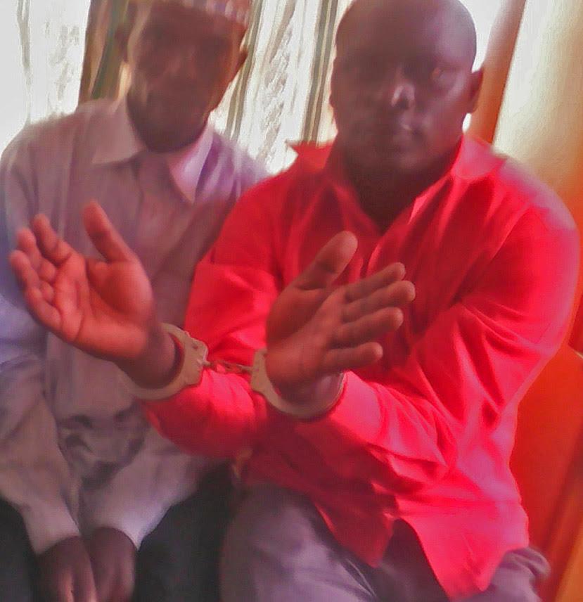 Hassan Muwanguzi (handcuffed) with accuser Nghangha Mubakali during police investigation. (Morning Star News)
