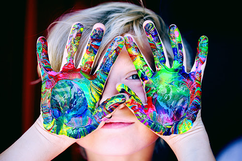 Child holds covered in colorful paint swirls in front of face, smiling