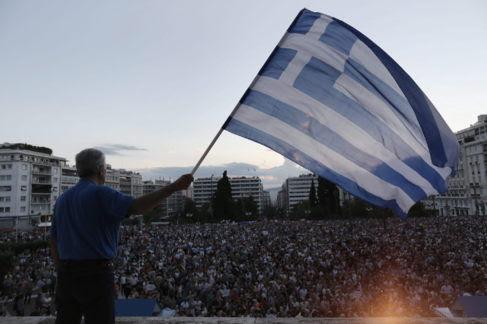 Un manifestante ondea una bandera griega, a las afueras del Parlamento...