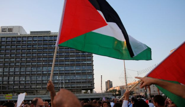 Demonstrators waving Palestinian flags at Rabin Square ahead of a march against the nation-state law, August 11, 2018.