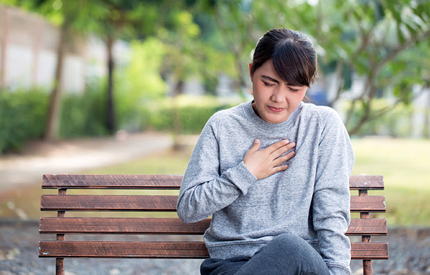 A woman sitting on a park bench holding her chest.