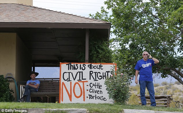 JOining the cause: Steven Kelly (R) talks on a phone as he stands by a protest signs he posted on his house as his soon Sean Kelly (L), looks on west of Mesquite, Nevada