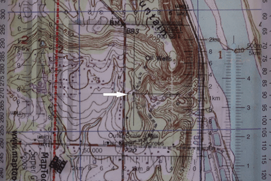 military protractor on top of topo topographic map