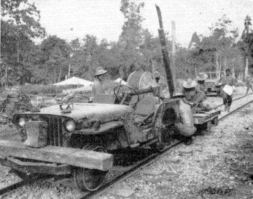 SPECIALLY-EQUIPPED rail Jeep strings signal wire along the railroad from Pinwe to Naba Junction in Burma. Operators are men of the 96th Signal Bn., Co. A. U.S. Army photo taken Dec. 15, 1944.