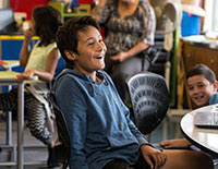 A young Māori boy looking happy in his classroom