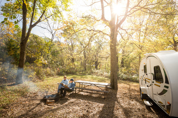 An older couple reads near a campfire beside their small RV camper.