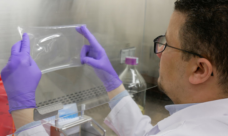 Researcher Abdelrahim Hassan examining the composite film. Image courtesy of Penn State University.