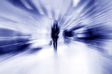 Blurred image of person walking toward camera.