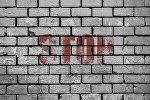 Una pared de ladrillos con palabra stop