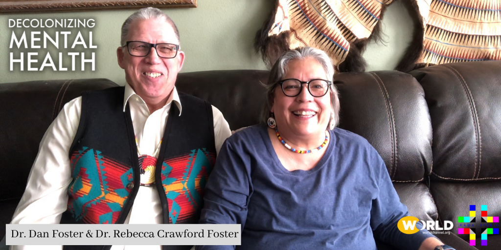 Indigenous mental Healthcare practitioners Dr. Dan Foster & Dr. Rebecca Crawford Foster sit side by side on a couch. Both smile, have grey hair and wear glasses. He wears a woven vest with a traditional pattern and traditional earrings and a necklace. Click here for their interviews.