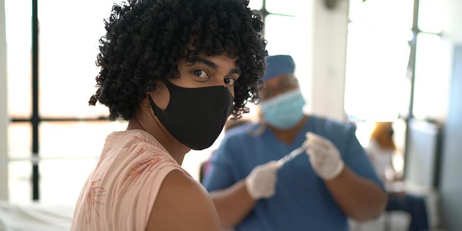 foto de un joven esperando recibir su vacuna COVID-19