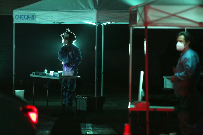 A night-time photo shows actors in protective gear rehearsing a COVID-themed play in a parking lot.