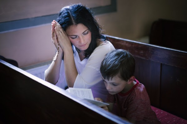 Mother praying with child in church.