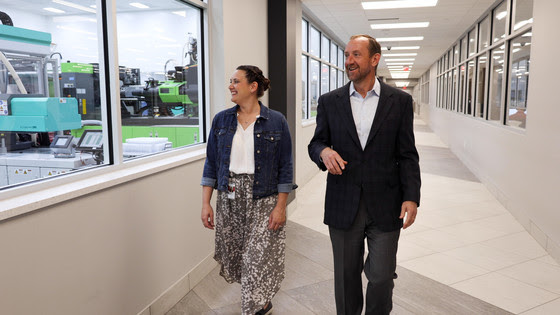Adult male and female walk smiling down the hall of manufacturing facility