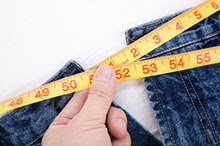 A hand holding a tape measure next to a pair of jeans.