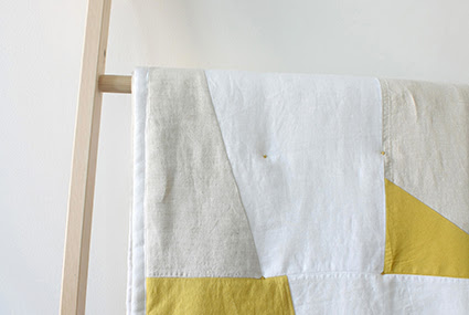 A photograph of a quilt by Woolgathering. It is displayed on a wooden ladder against a white wall, and is made of beige, white and yellow fabric.