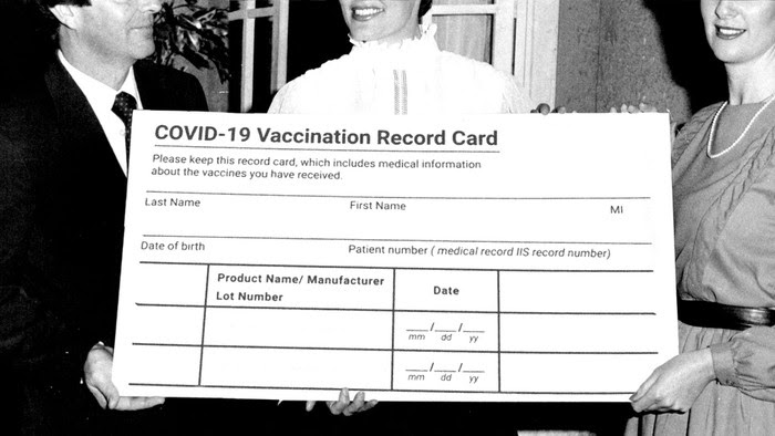 Three well-dressed people hold an enormous, fake COVID-19 vaccination card.