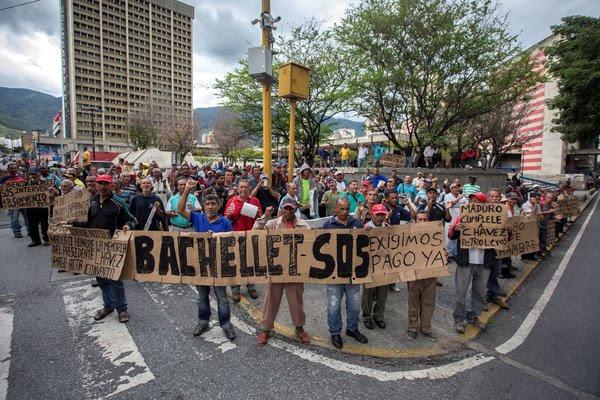 """Protestas durante la visita de Michelle Bachelet a Venezuela. El gobierno de Nicolás Maduro respondió al informe con críticas de que las fuentes del reporte son """"carentes de objetividad""""."""