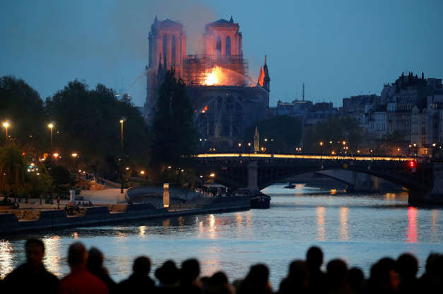 Slide 15 of 31: People watch as fire fighters douse flames of the burning Notre Dame Cathedral in Paris, France April 15, 2019. REUTERS/Charles Platiau - RC17DCBE9F60