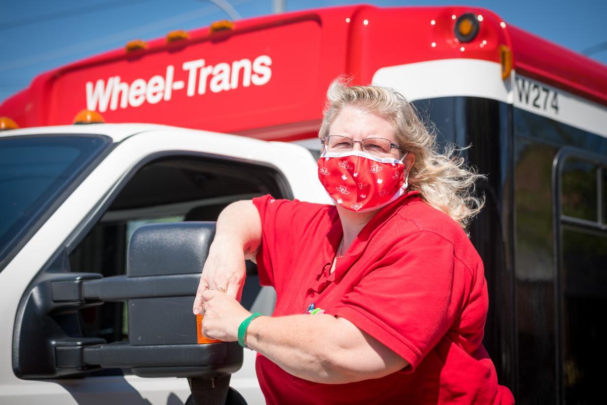 A TTC employee stands beside a Wheel-Trans vehicle