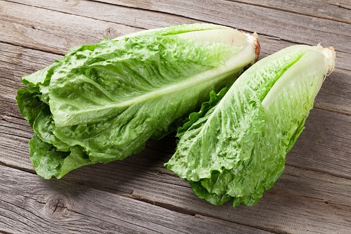 Two heads of romaine lettuce on a wooden table.