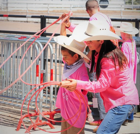 Dressed in pink shirts and cowboy hats, a teacher helps an elementary student learn how to rope at the Challenge Rodeo.