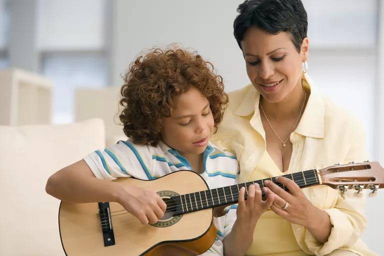 Mother showing son how to play guitar