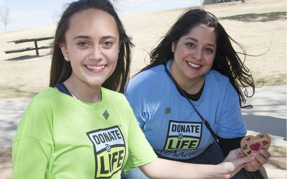 2018 Baldrige Award Recipient Donor Alliance photo showing two female volunteers outside holding a heart with Donate Life shirts.