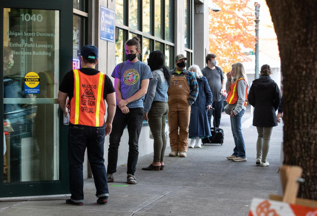 Voters stand in line outside the Multnomah County Duniway-Lovejoy Elections Building. Two election workers help in orange vests.