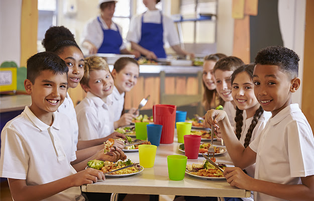 Children eating lunch in a noisy school cafeteria.