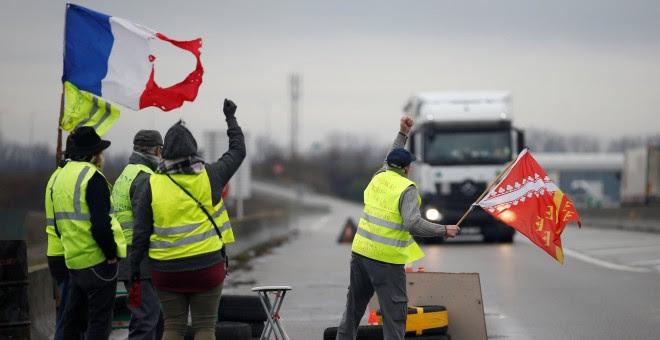 Miembros del movimiento de los chalecos amarillos, el símbolo de una protesta de los conductores franceses contra los altos precios del combustible diesel, ocupan una rotonda en Roppenheim, Francia. REUTERS / Vincent Kessler