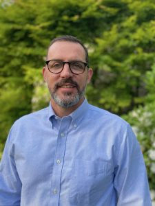 Tom Flanagan stands smiling, wearing a blue button-down shirt and glasses, in front of a tree