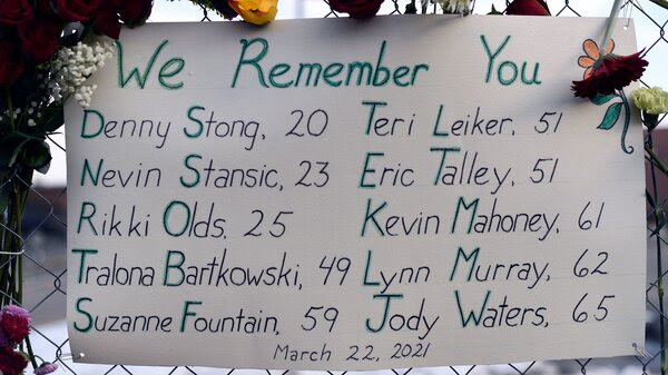 A sign framed with flowers lists the victims' names on the fence outside a King Soopers grocery store in Boulder, Colo. The suspected gunman is making his first court appearance on Thursday.