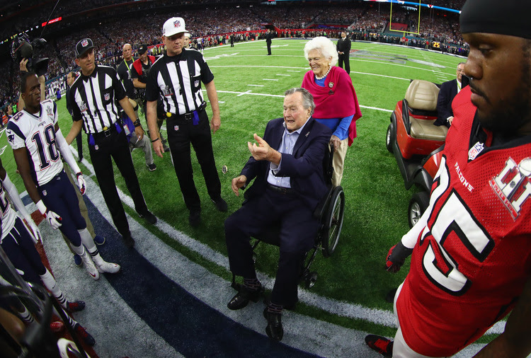 George H.W. Bush flips the coin, with wife Barbara. (Al Bello/Getty Images)</p>